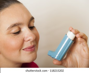 Cute young female looking her new asthma inhaler