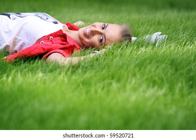 Cute young female lying on grass field at the park