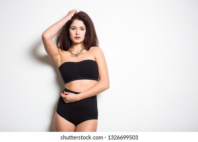 Cute, young female model posing in front of a white wall