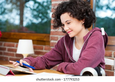Cute young female teen doing schoolwork at home on tablet.