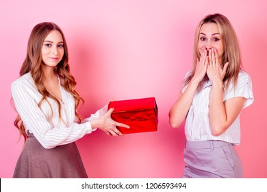 cute and young female teenager person daughter gives a Christmas box with a gift to surprised delight mom womam on a pink background in studio . concept of celebrating new year 2019