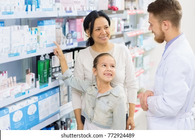 Cute young girl asking harmacist about medicine at the drugstore while shopping with her mother consultation kids children positivity happiness parenting professional trustworthy experienced doctor