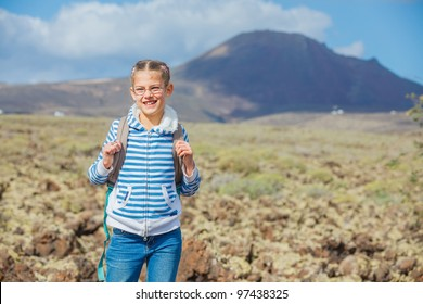 Cute young girl with backpack have trip in the mountains with volcano