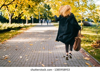 cute Young girl in a black coat and striped pants runs skipping along road in an autumn Park waving a big red bag. Charming lady in autumn in autumn garden. Cheerful woman on background of foliage