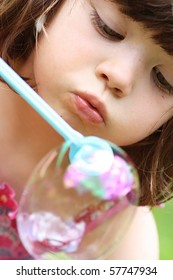 Cute Young Girl Blowing a Bubble