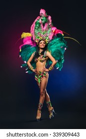 Cute young girl in bright colorful carnival costume on dark background