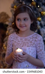cute young girl in christmas with a candle in her hands