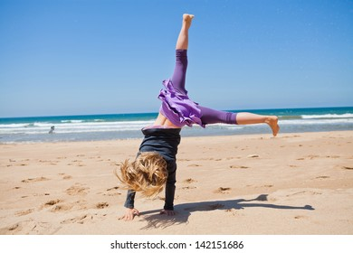 Cute young girl doing cartwheel in sand at beach with blue sky and ocean in background