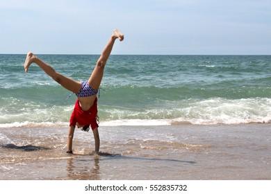 Cute young girl doing cartwheel at a beach in Brazil.