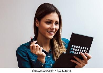 Cute young girl doing makeup.