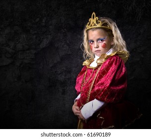 Cute young girl dressed up in a princess costume on a black background.