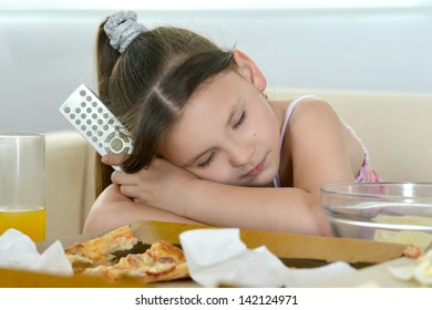 cute young girl eating pizza at home