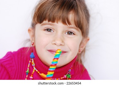 A cute young girl eating a sucker