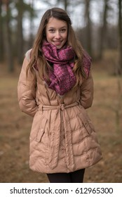 Cute young girl in a gray coat and color scarf stands in the forest in  autumn cb33d04af