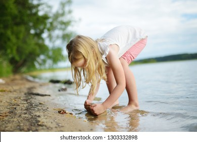 Cute young girl having fun on a sandy lake beach on warm and sunny summer day. Kid playing by the river. Summer activities for children.