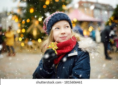 Cute young girl having gingerbread cookie on traditional Christmas fair in Riga, Latvia. Child enjoying sweets, candies and gingerbread on Xmas market. Winter time with family and kids.