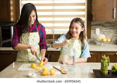 Cute young girl and her mother cutting and squeezing lemons to make lemonade at home