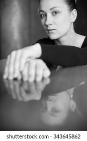 Cute young girl with her reflection at the table. monochrome soft focus portrait