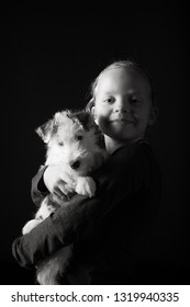 Cute young girl and her wire fox terrier puppy in the studio against a black background in monochrome