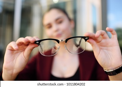 cute young girl holding glasses close-up. Optics, blzorukost, farsightedness, astigmatism.