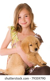 A cute young girl holding a Golden Retriever Puppy on an isolated white background