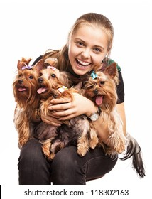 Cute young girl holding Yorkshire terrier dogs on her lap over white