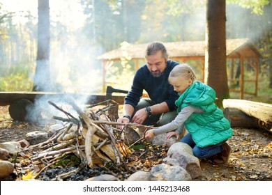 Cute young girl learning to start a bonfire. Father teaching her daughter to make a fire. Child having fun at camp fire. Camping with kids in fall forest. Family leisure with kids at autumn.