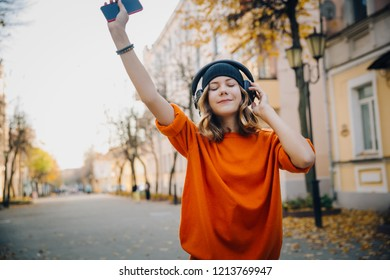 cute young girl listening music in headphones, dansing and holding mobilephone in hand, urban style, stylish hipster teen in black hat listen music on autumn city street, orange crazy street style