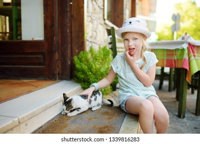 Cute young girl petting a friendly Greek cat on warm and sunny summer day during family vacations in Kalavryta village, Greece