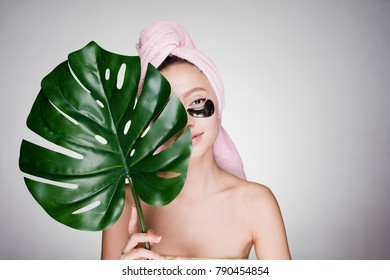 cute young girl with a pink towel on her head holding a green leaf, under the eyes of black patches, day spa