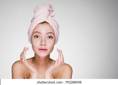 cute young girl with pink towel on her head applying white nourishing cream on face