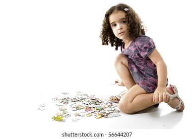 cute young girl playing with puzzle .