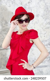 Cute young girl in a red hat and sunglasses