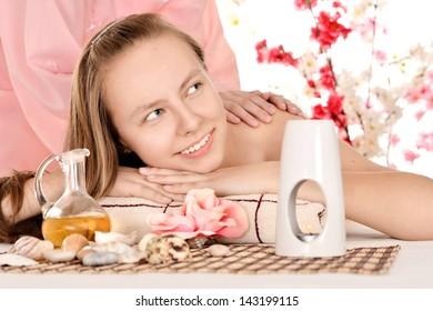 cute young girl relaxing in spa salon