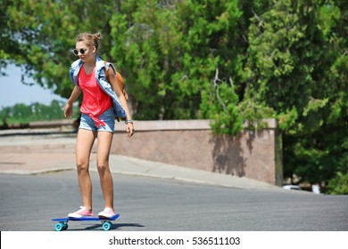 Cute young girl riding skateboard on street