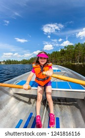 Cute young girl rowing a rowboat on a lake with blue summer sky in the background.
