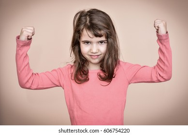 Cute young girl showing her strong arms
