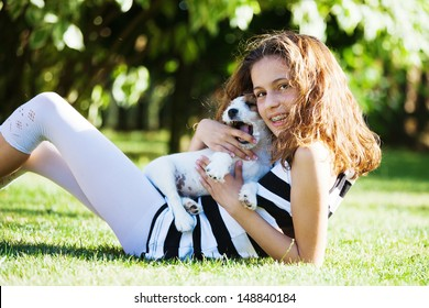 cute young girl sits on the grass with a biting Parson Russell Terrier puppy