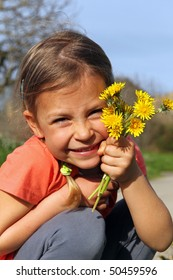 Cute young girl smiling and holding a bunch of yellow daisy flowers
