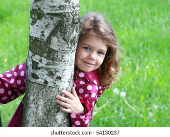 Cute young girl smiling and hugging a birch-tree trunk