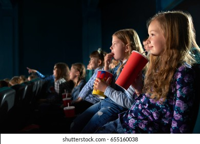 Cute young girl smiling joyfully sipping her drink watching a movie at the cinema copyspace entertainment positivity children childhood relax activity leisure hobby beverage snack concept.
