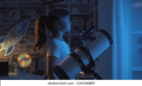 Cute young girl stargazing at night with a telescope, she is looking away: imagination and childhood concept