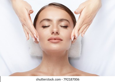 Cute  young girl with thick eyebrows and perfect skin doing facial massage, closed eyes, relaxing, beauty photo concept, stress free.