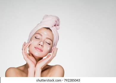 a cute young girl with a towel on her head puts a nourishing cream on her face, her eyes are closed, she enjoys