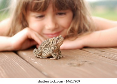 A cute young girl watching a toad