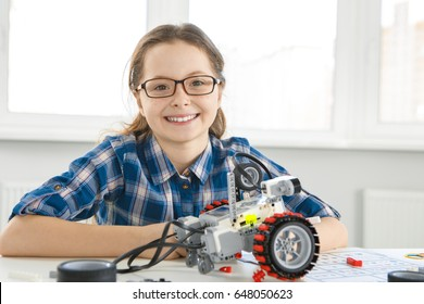 Cute young girl wearing glasses smiling to the camera sitting in front of a robot copyspace education learning technology science robotics mechanics classes intelligent smart skillful leisure hobby