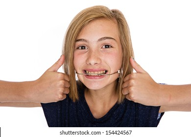 A cute young girl wearing orthodontic headgear