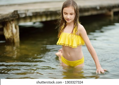 Cute young girl wearing swimsuit playing by a river on hot summer day. Adorable child having fun outdoors during summer vacations. Water activities for kids.