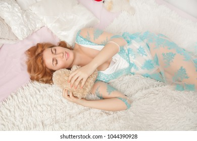 cute young girl wearing transparent pyjamas lies with small brown teddy bear toy on the white bed in her bedroom in the morning