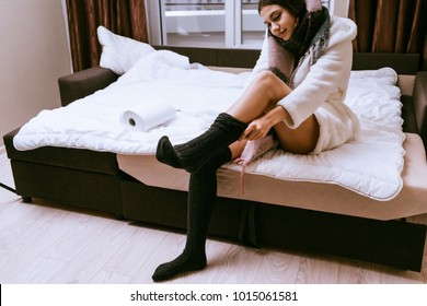 cute young girl in a white robe sits on the bed, puts on warm socks